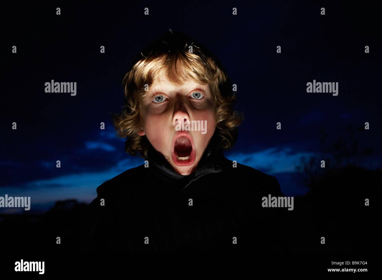 Boy making faces avec torche Banque D'Images