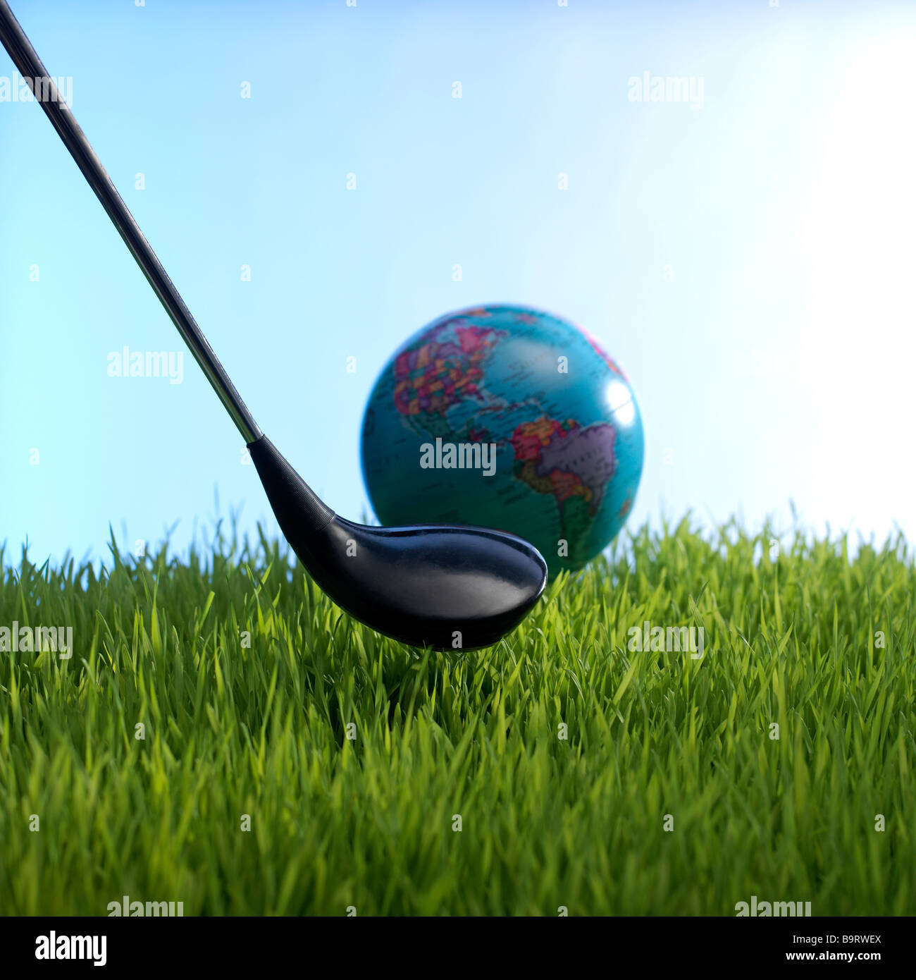 Globe and gold club in grass Photo Stock