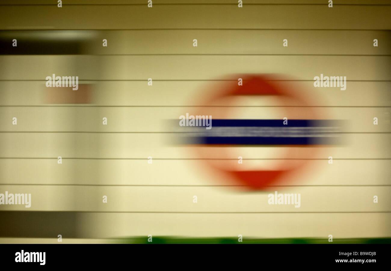 Train de tube d'accélérer au-delà d'un métro de Londres signe. Photo Stock