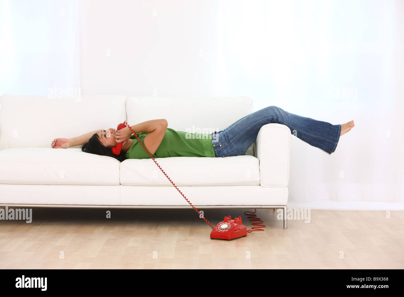 Woman on couch talking on retro téléphone Photo Stock