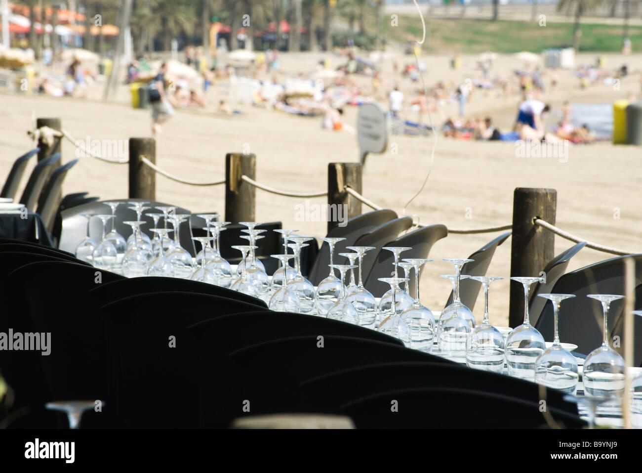 Verres à vin mis à l'envers en rangées sur table au restaurant en bord de mer Banque D'Images