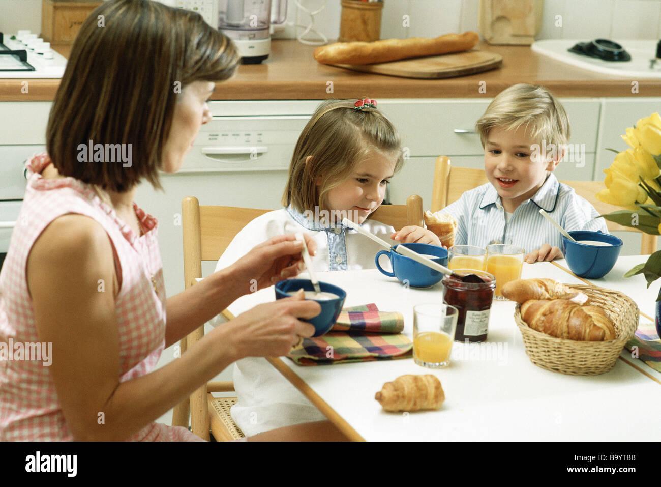 Famille assis à table pour le petit déjeuner Photo Stock