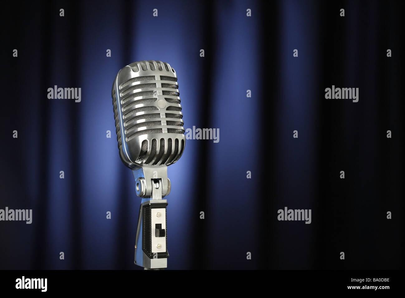 Vintage microphone avec rideau bleu foncé background Photo Stock