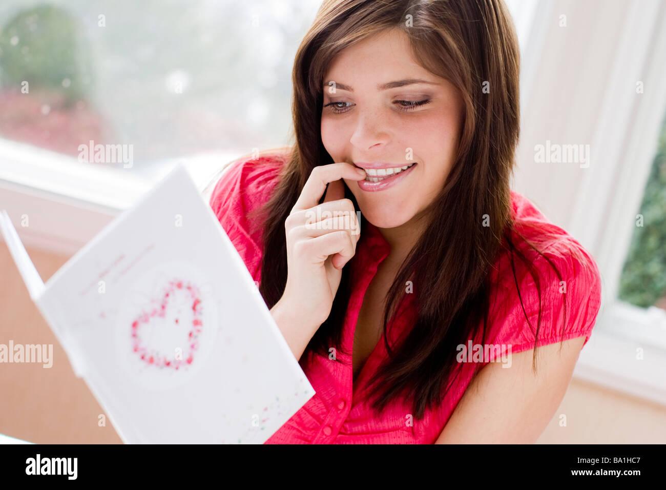 Femme regardant une carte de Saint-Valentin Photo Stock