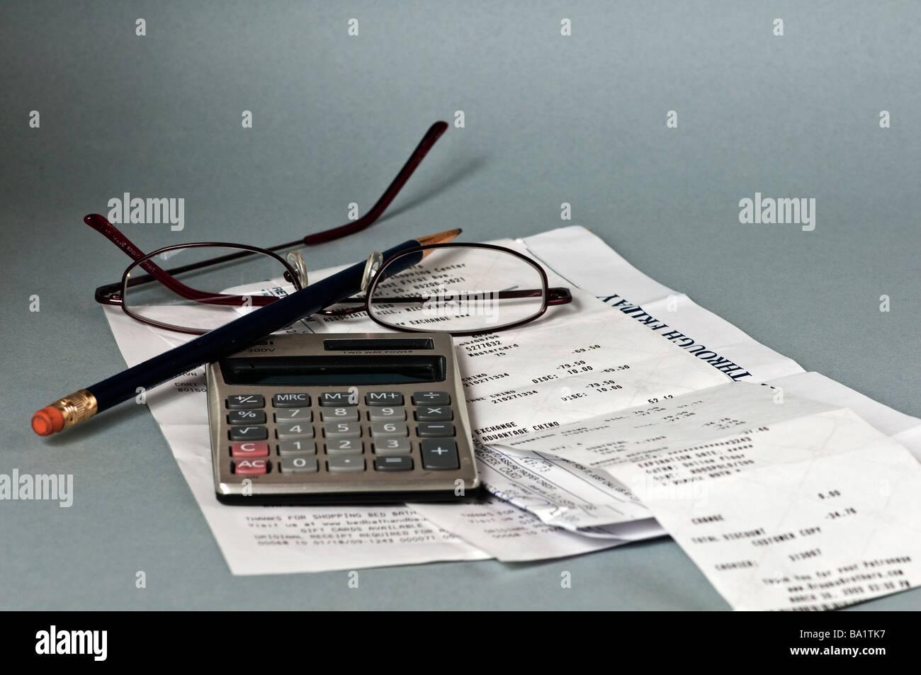Calculatrice sur haut de reçus avec crayon et lunettes de lecture Photo Stock