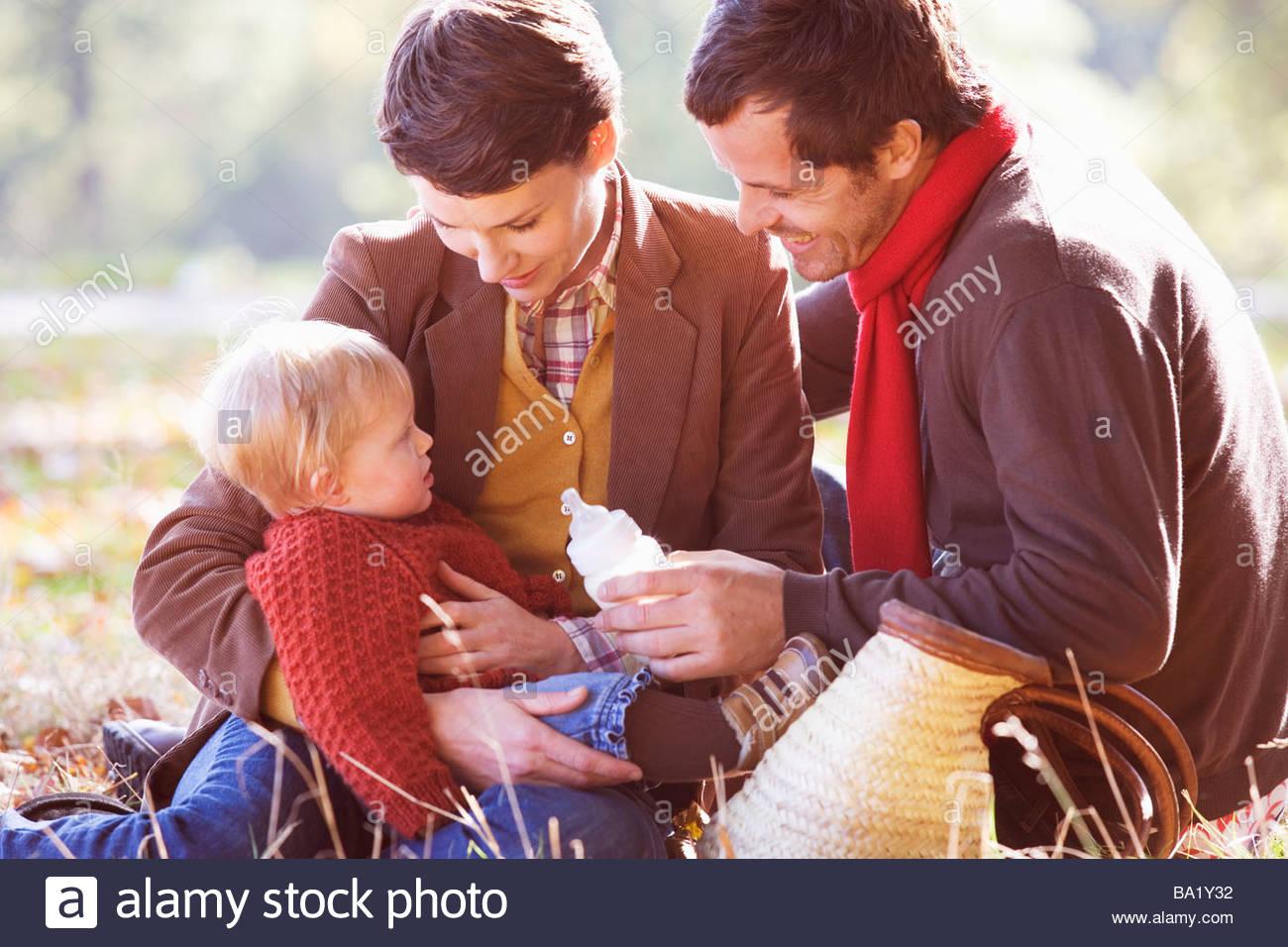 Une jeune famille assis sur l'herbe, père de l'enfant Photo Stock