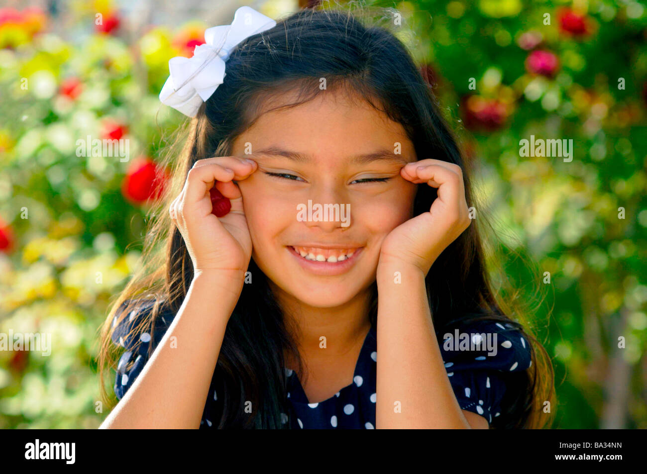 Cute young hispanic female clown et faire les yeux chinois Photo Stock