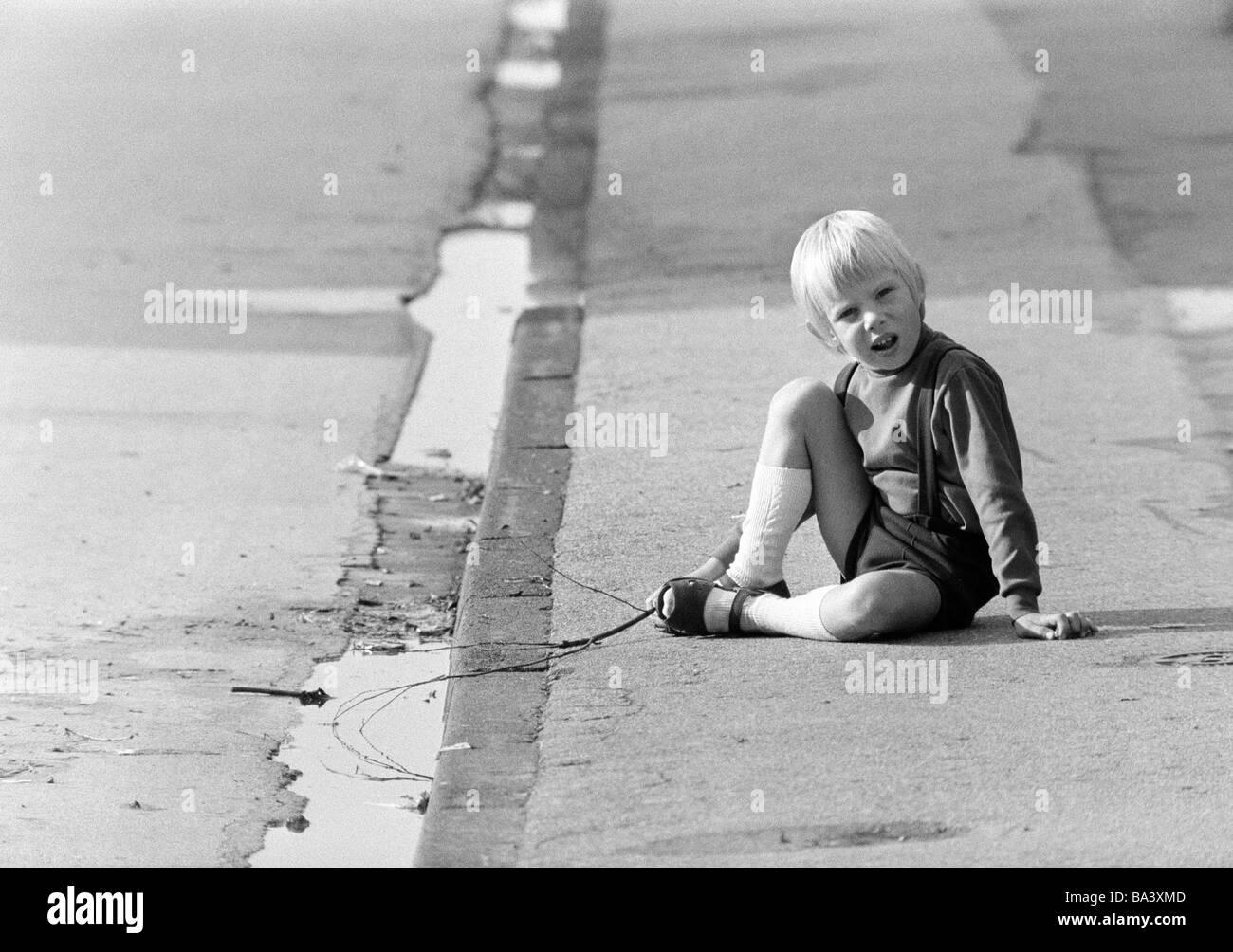 ann u00e9es 70  photo en noir et blanc  les gens  les enfants  petit gar u00e7on est assis sur un trottoir