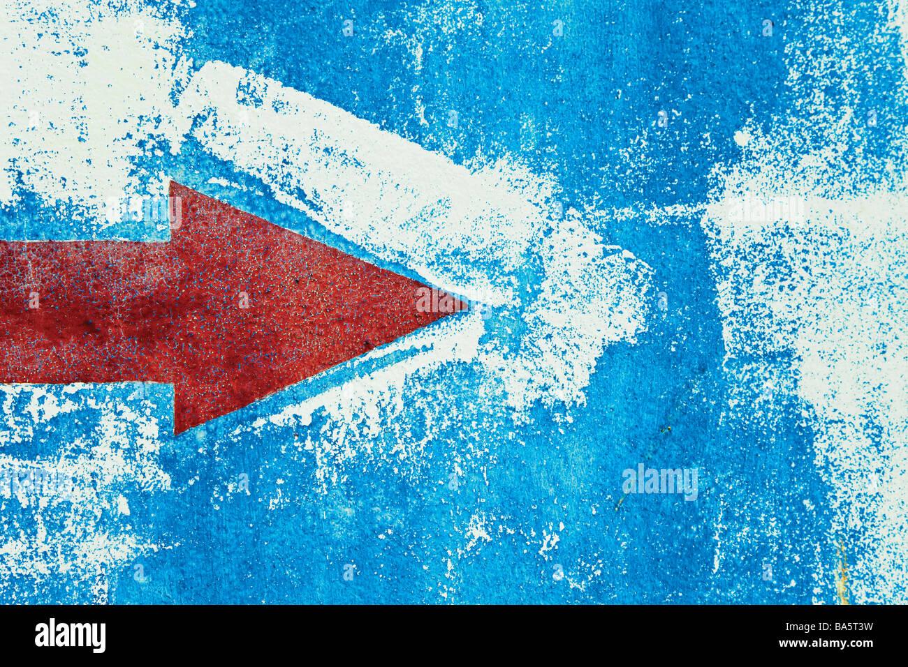 Flèche rouge peint sur mur bleu Photo Stock