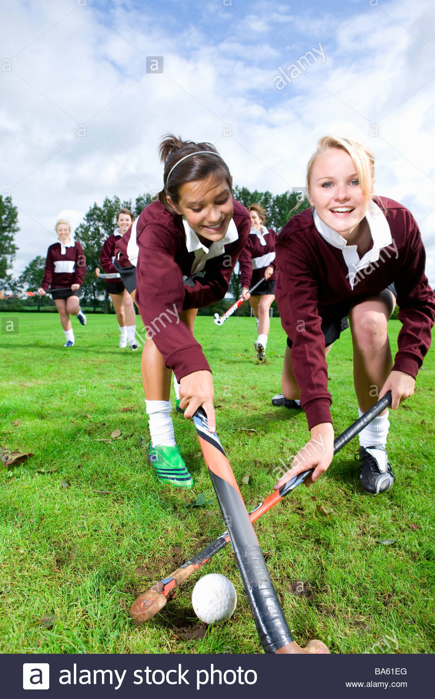 Portrait of smiling teenage girls playing field hockey Photo Stock