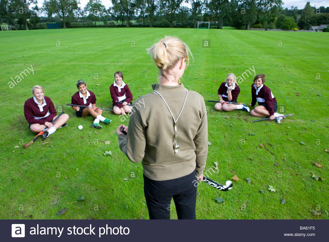 Debout devant l'entraîneur de l'équipe de hockey de champ adolescente Photo Stock