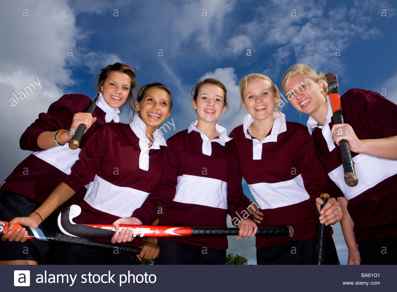 Portrait of smiling teenage girls holding field hockey stick Photo Stock
