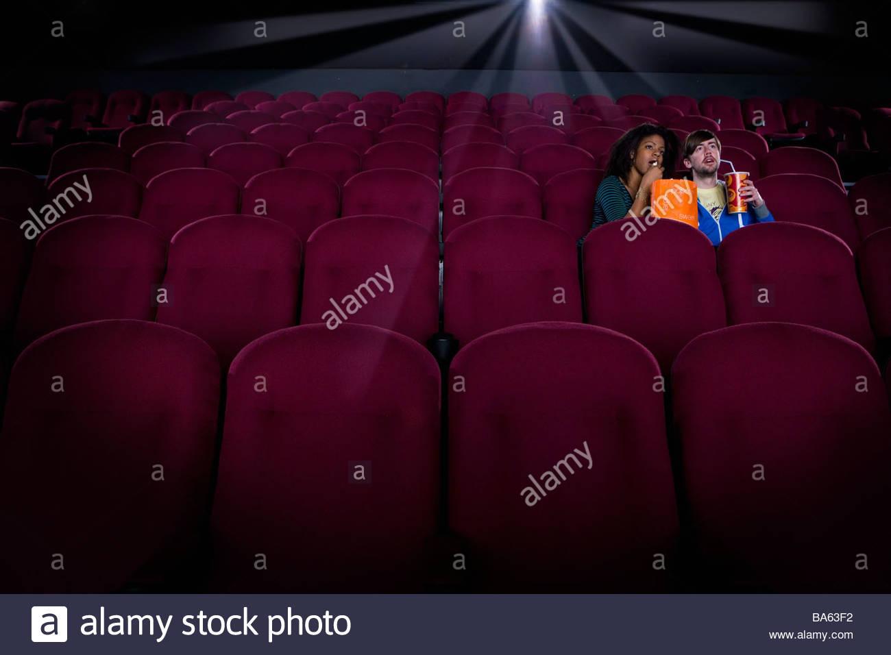 Couple in empty cinema avec boisson et pop-corn Photo Stock
