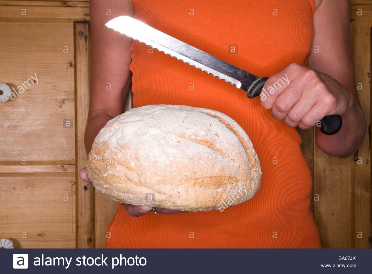 Close up of woman holding miche de pain et un couteau dentelé Photo Stock