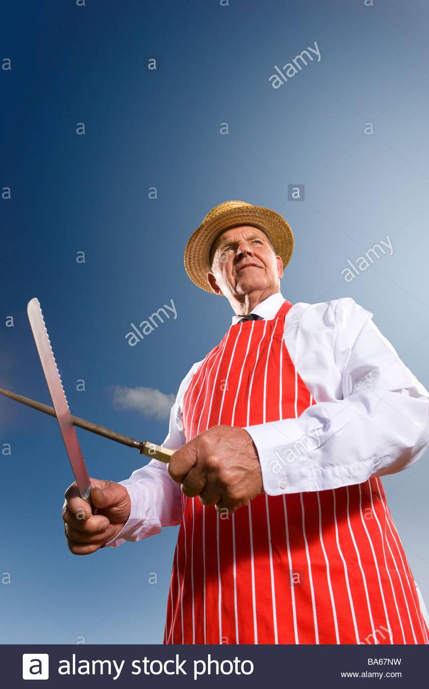 Portrait d'affûtage couteau dentelé boucher Photo Stock