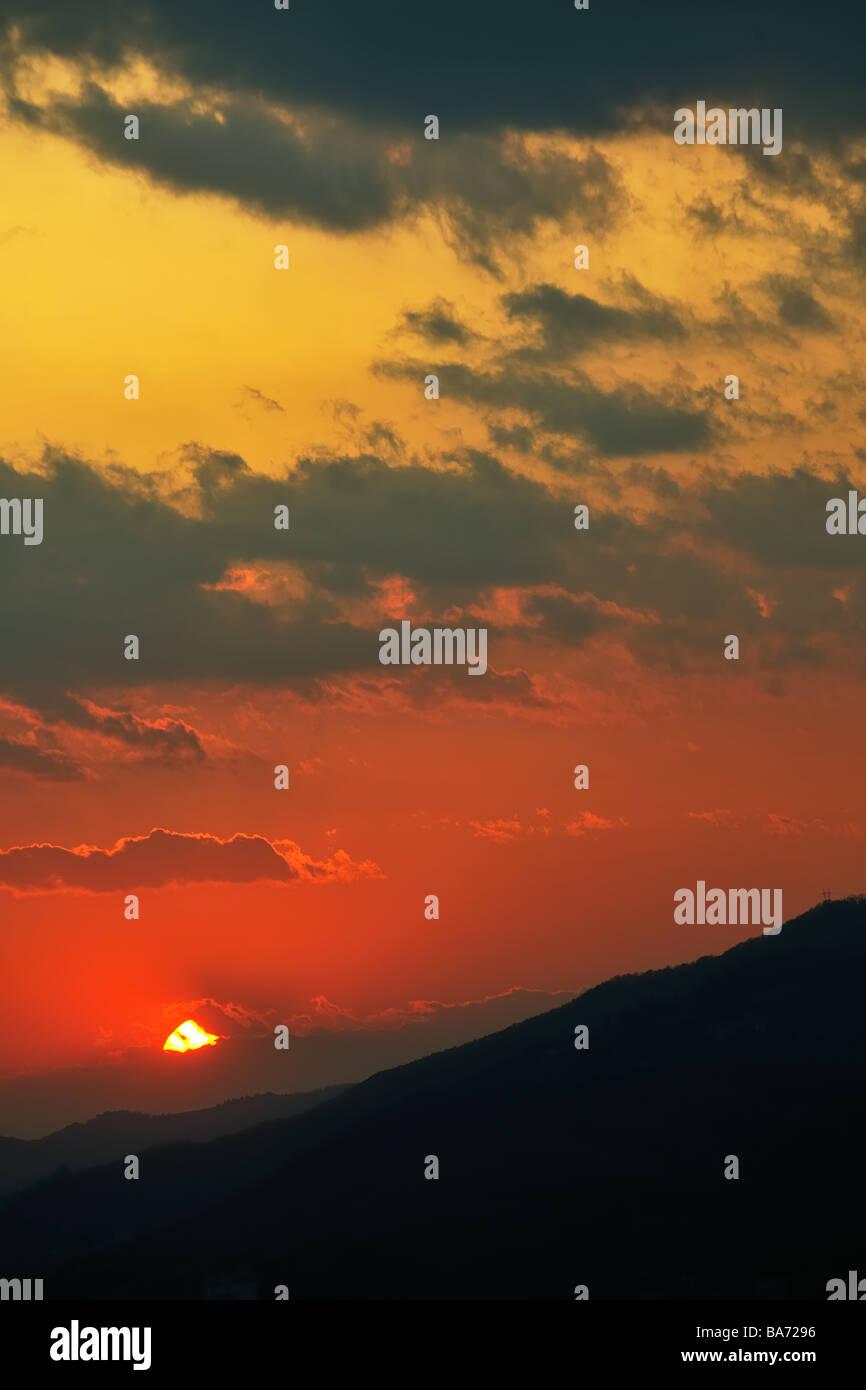 Soleil couchant lointain de disparaître à l'horizon enveloppée de nuages sur les silhouettes Photo Stock