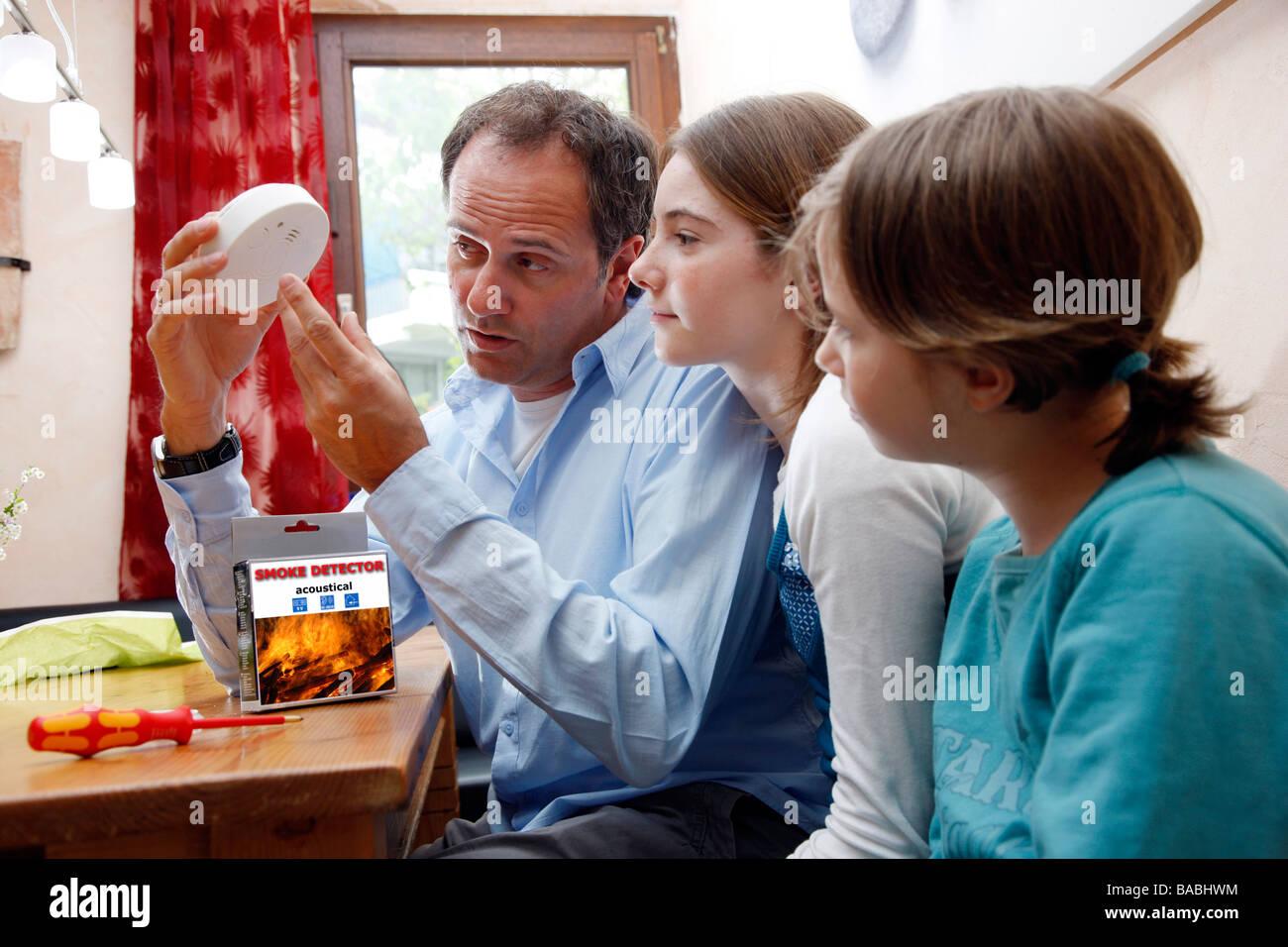 Un père explique un détecteur de fumée à ses filles. Prévention incendie dans une maison Photo Stock