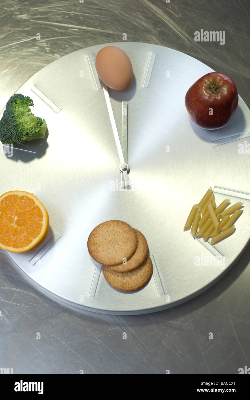 Contrôle de l'alimentation de l'horloge- pâtes, biscuits, oranges, pommes, oeufs et brocoli Photo Stock