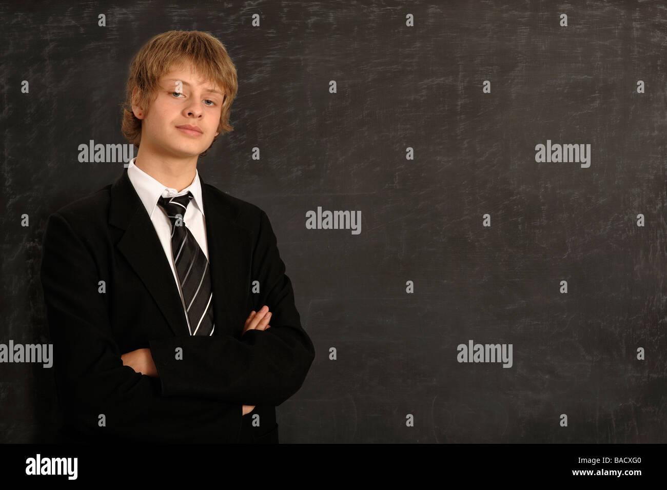 Écolier, debout devant un tableau noir Photo Stock