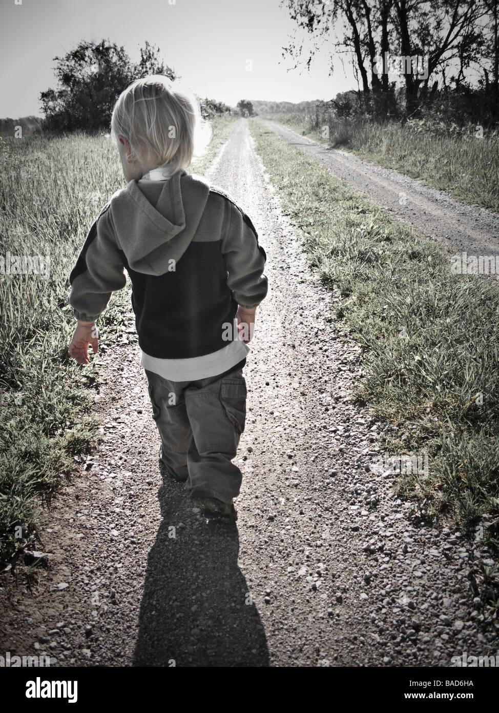 Tout-petit marche le long d'une route de gravier Photo Stock