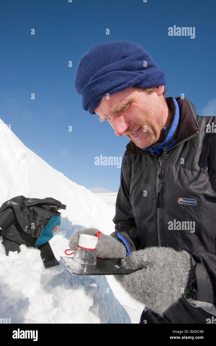 Un membre de l'Avalanche Information Service ressemble à des cristaux de neige pour aider à évaluer Photo Stock