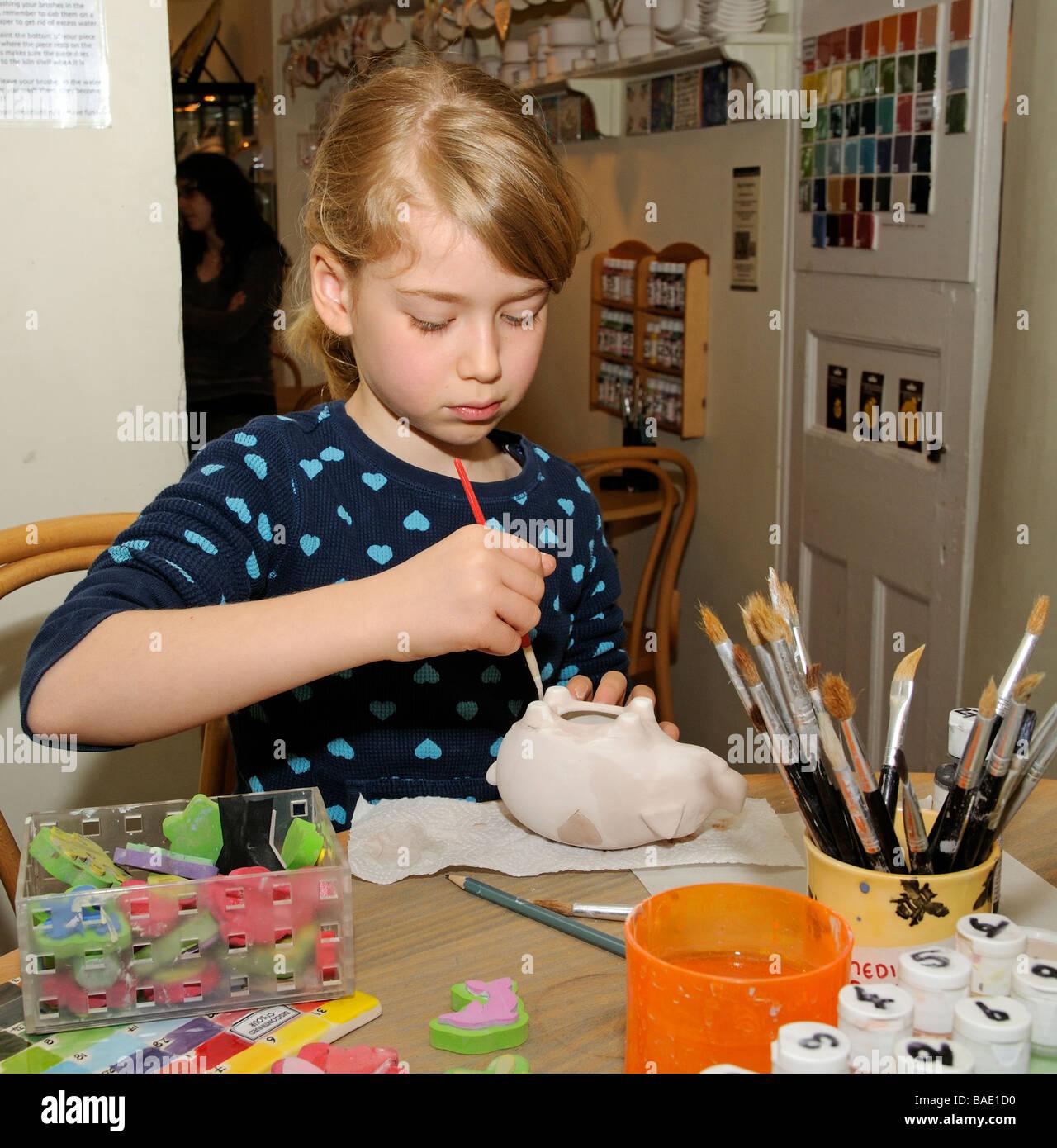 Cafe de la poterie et la peinture girl decorating une boîte d'argent argile Photo Stock