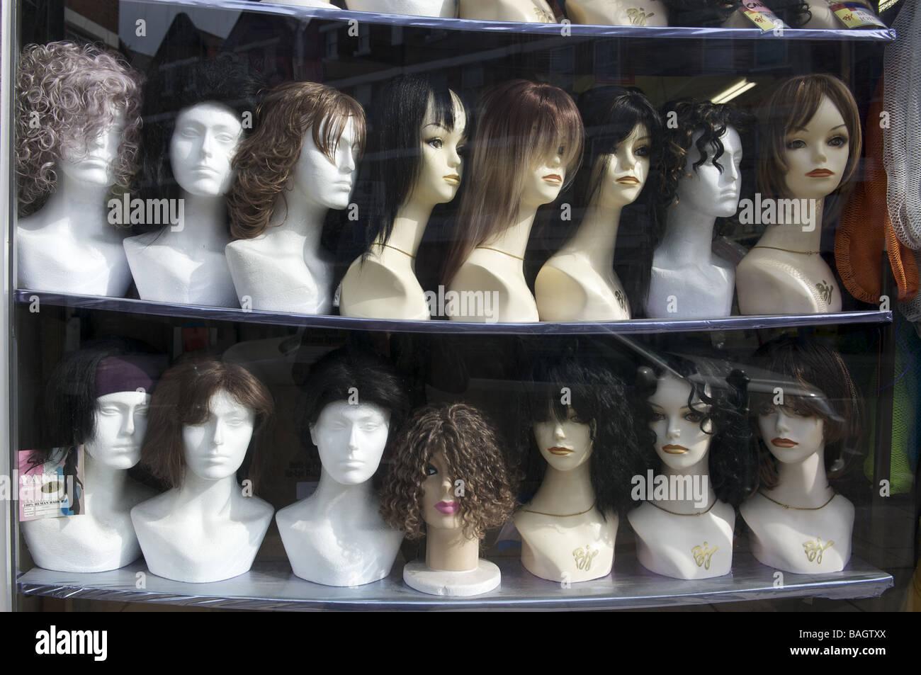 Perruque shop fenêtre avec rangées de perruques sur des mannequins Photo Stock