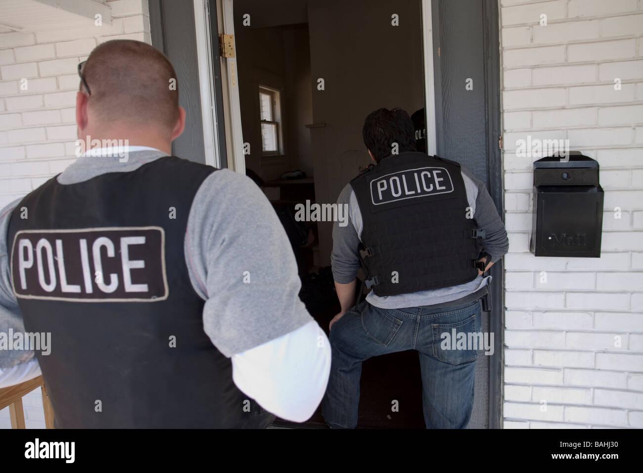 Les inspecteurs de la police de l'escouade des gangs entre dans un logement du suspect à la recherche de Photo Stock
