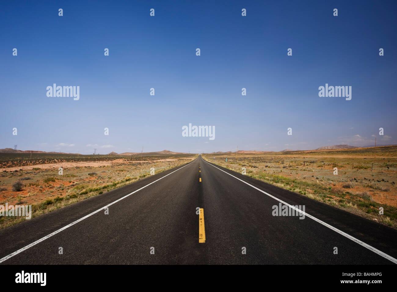 La route asphaltée en marche tout droit sur des kilomètres à l'horizon Photo Stock