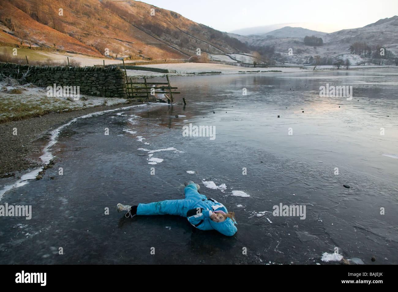 Jeune fille jouant sur la glace d'un lac gelé dans le Lake District, Cumbria, Royaume-Uni Photo Stock