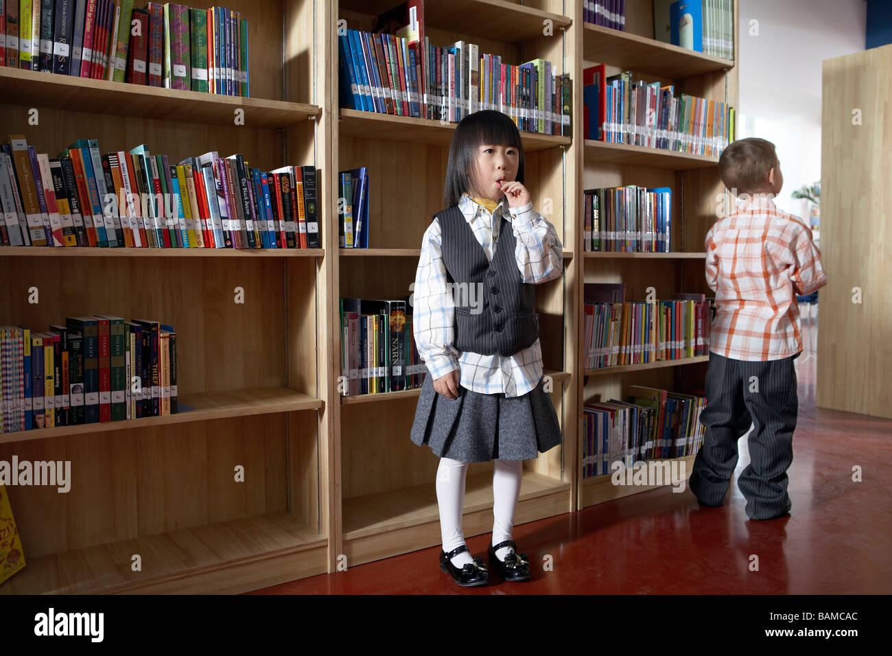 Enfants Standing In Library Banque D'Images