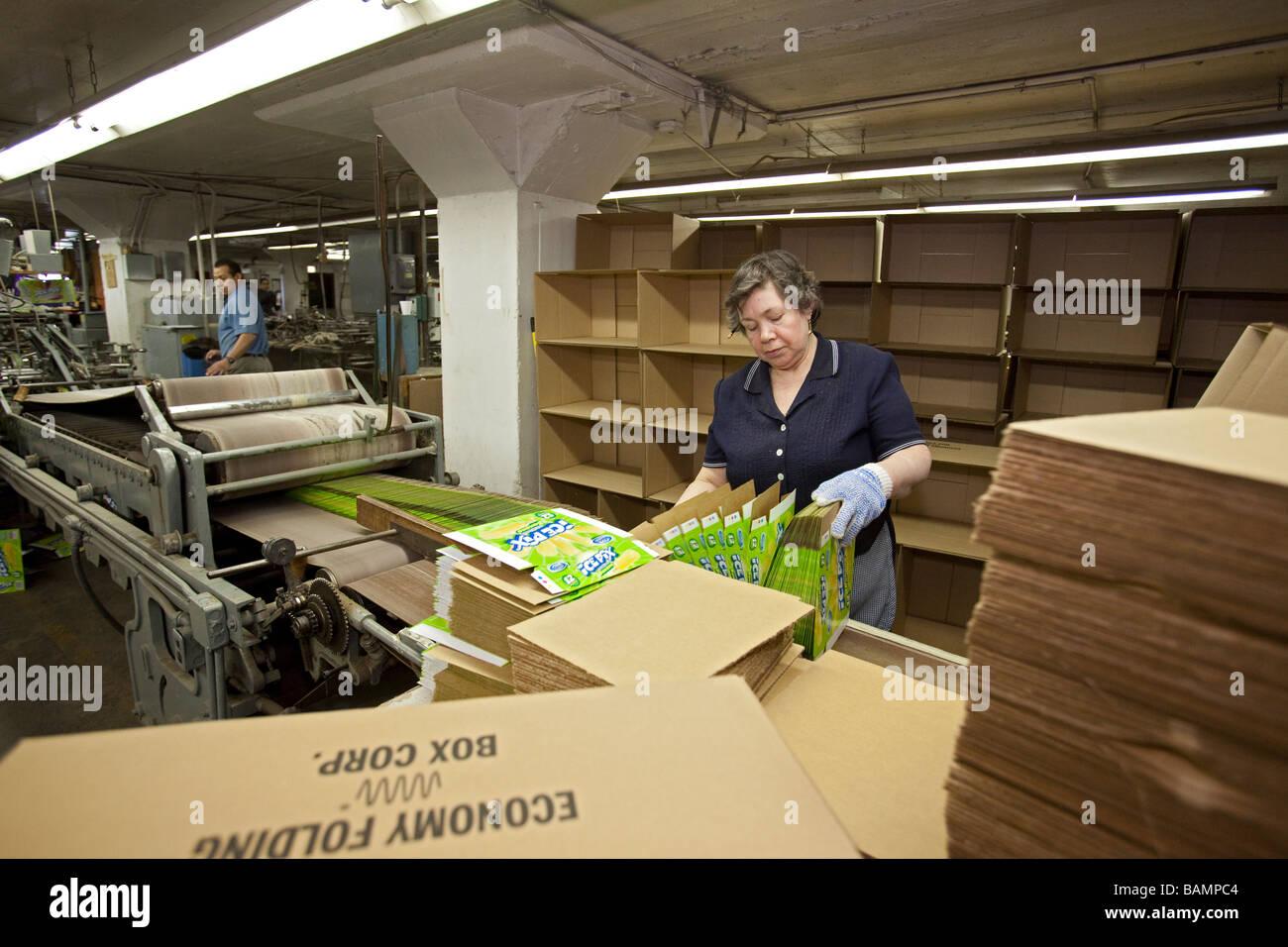 Les ouvriers effectuent des boîtes pour les produits de vente au détail Photo Stock
