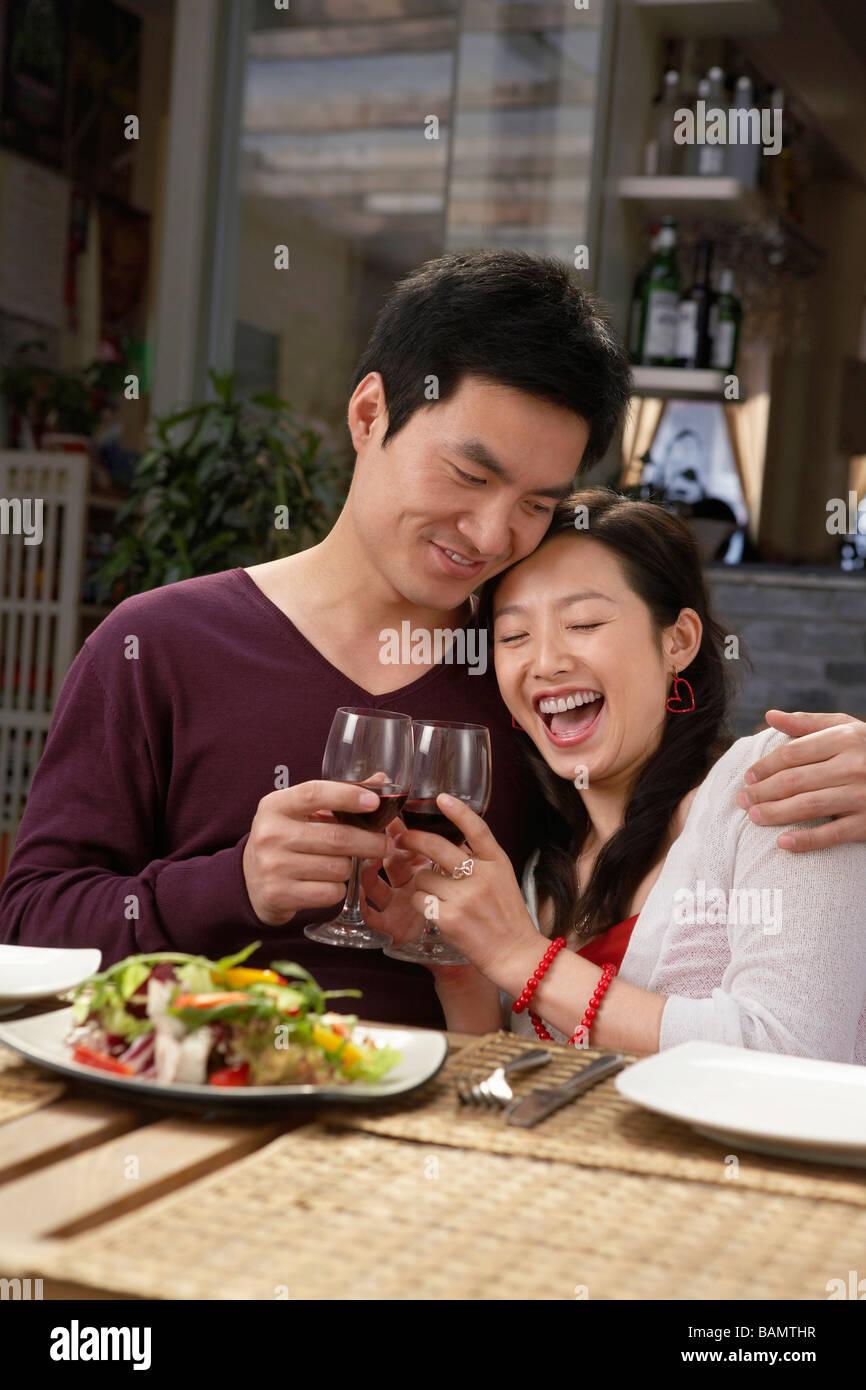 Jeune couple faire un toast lors d'un repas Photo Stock