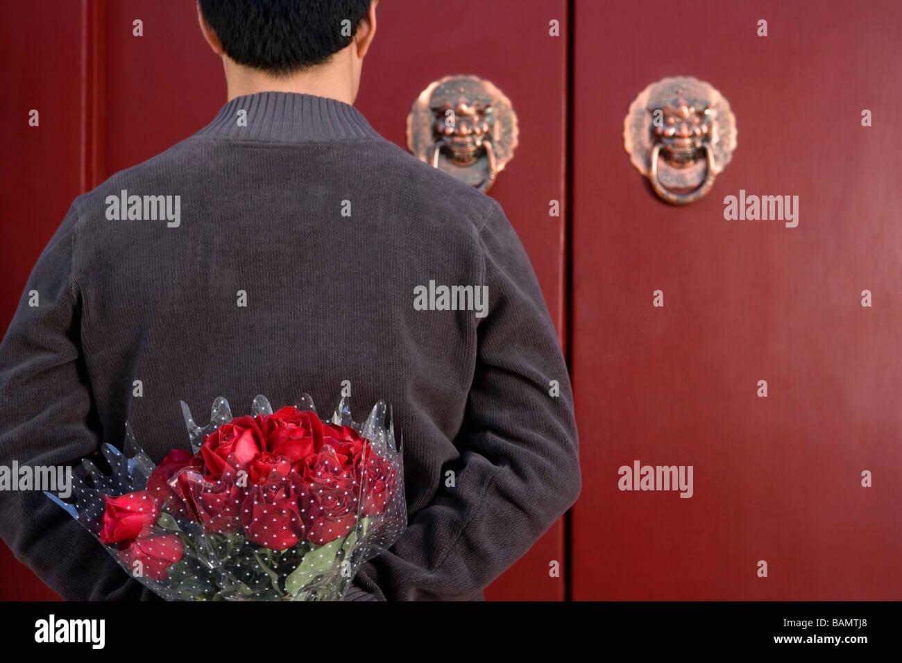 Jeune homme en attente à l'avant porte avec un bouquet de roses derrière son dos Photo Stock