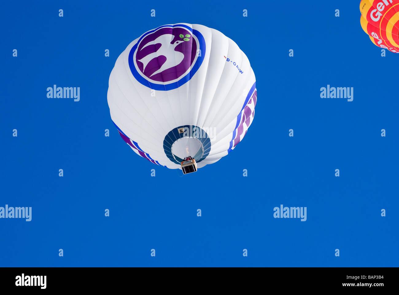 Ballons à air chaud s'élevant dans le ciel bleu clair au 2009 Chateau d oex montgolfières Banque D'Images