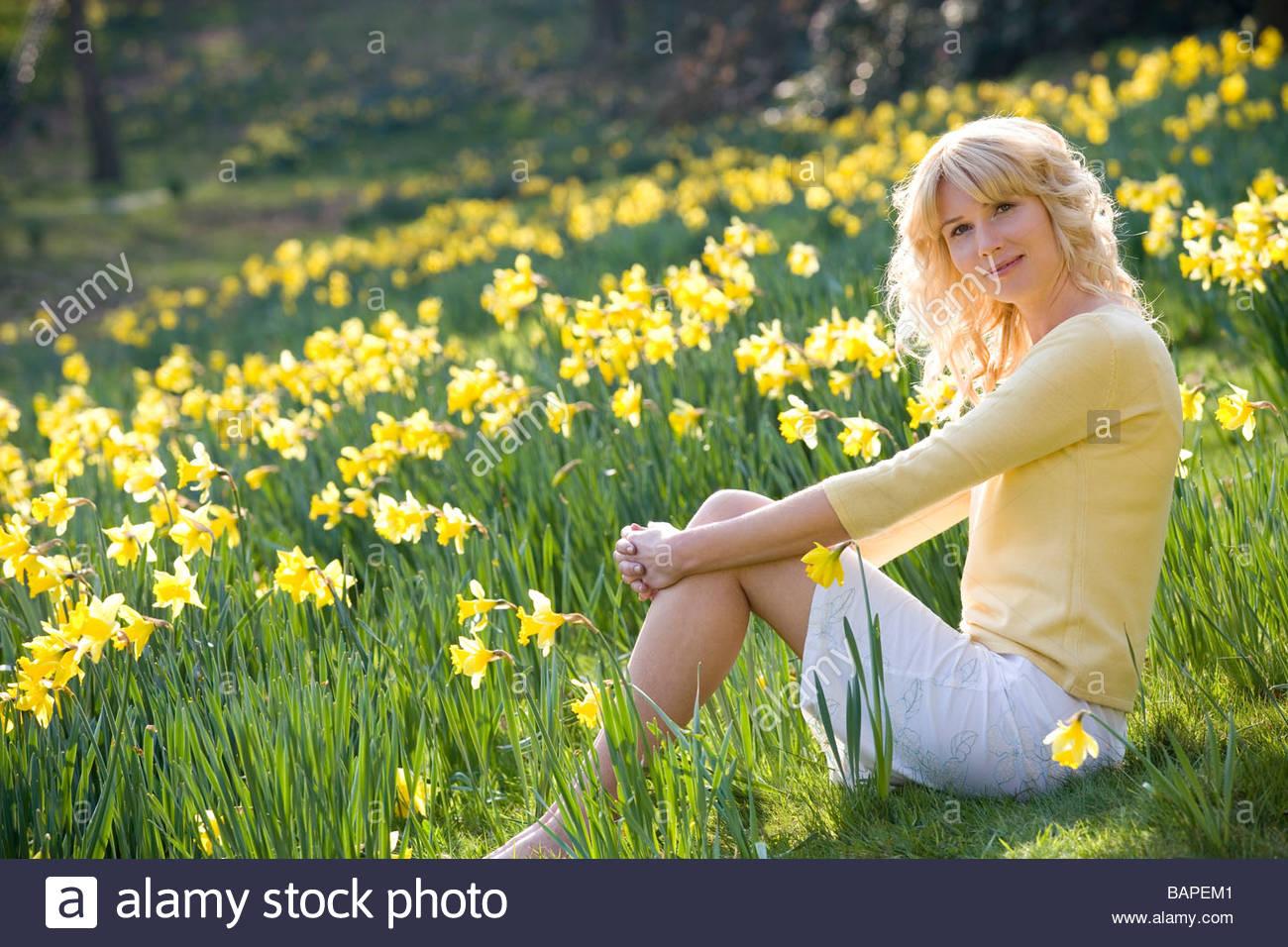 Une jeune femme assise entre les jonquilles Photo Stock