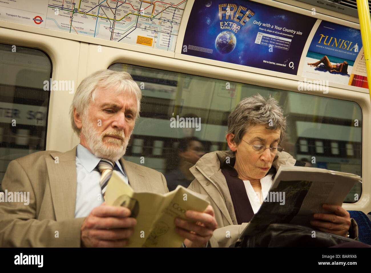 Couple reading, métro de Londres, Londres, Angleterre Photo Stock