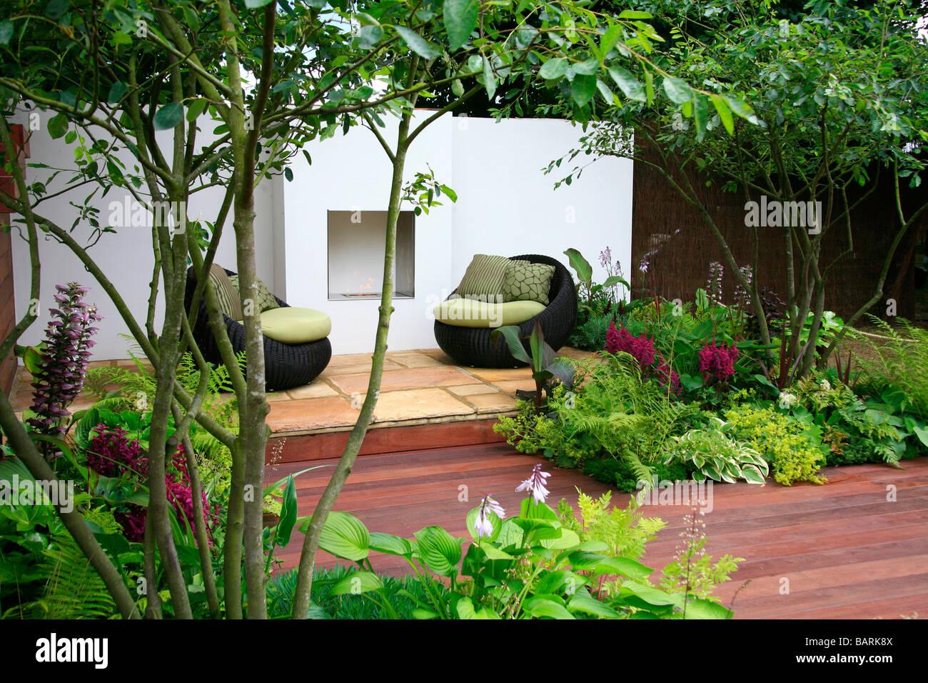 Petit jardin avec terrasse en bois et bordures plantées avec ...