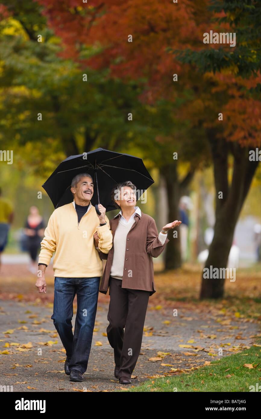 African couple walking avec parapluie en automne Banque D'Images