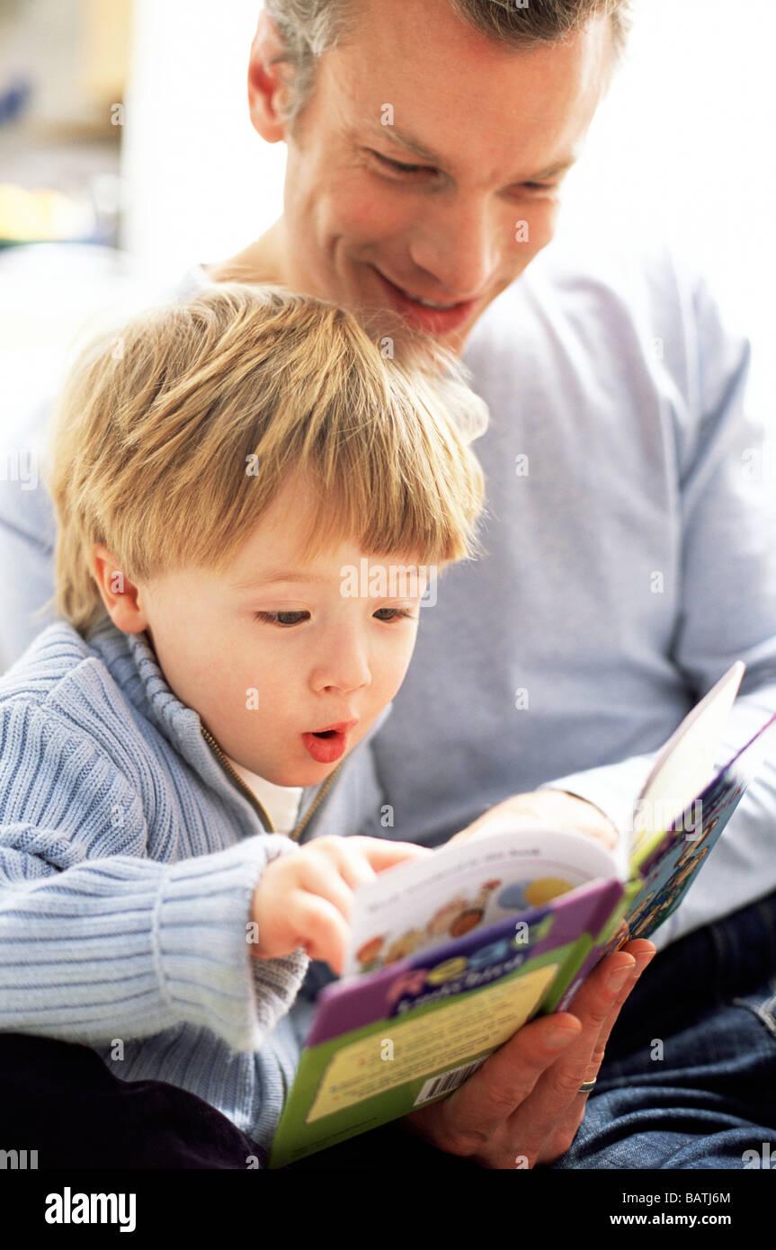 La paternité. Trois ans excité de lire un livre avec son père. Banque D'Images