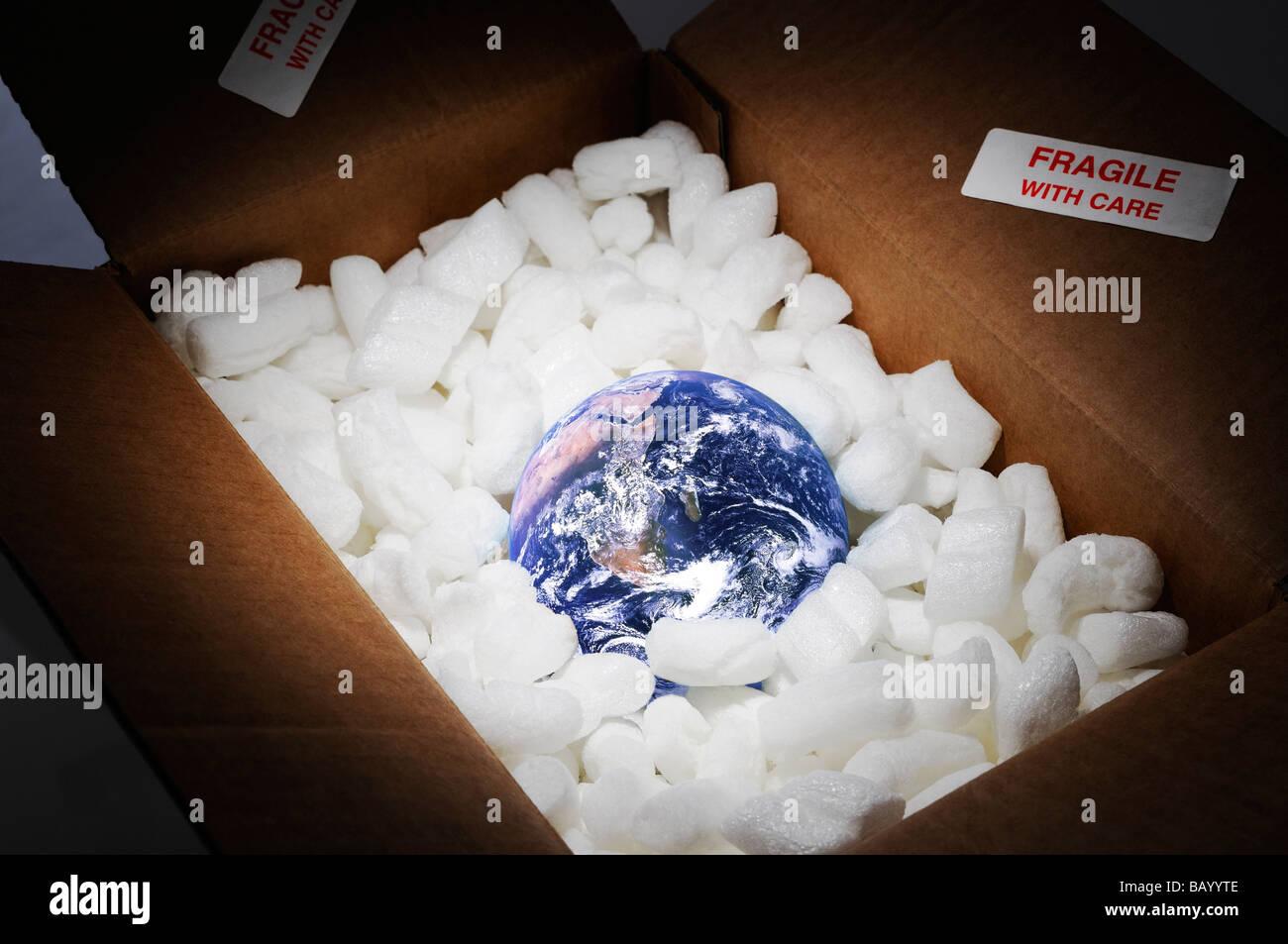 La planète Terre dans la boîte de carton ouvert entouré d'emballage protecteur et marqué Photo Stock