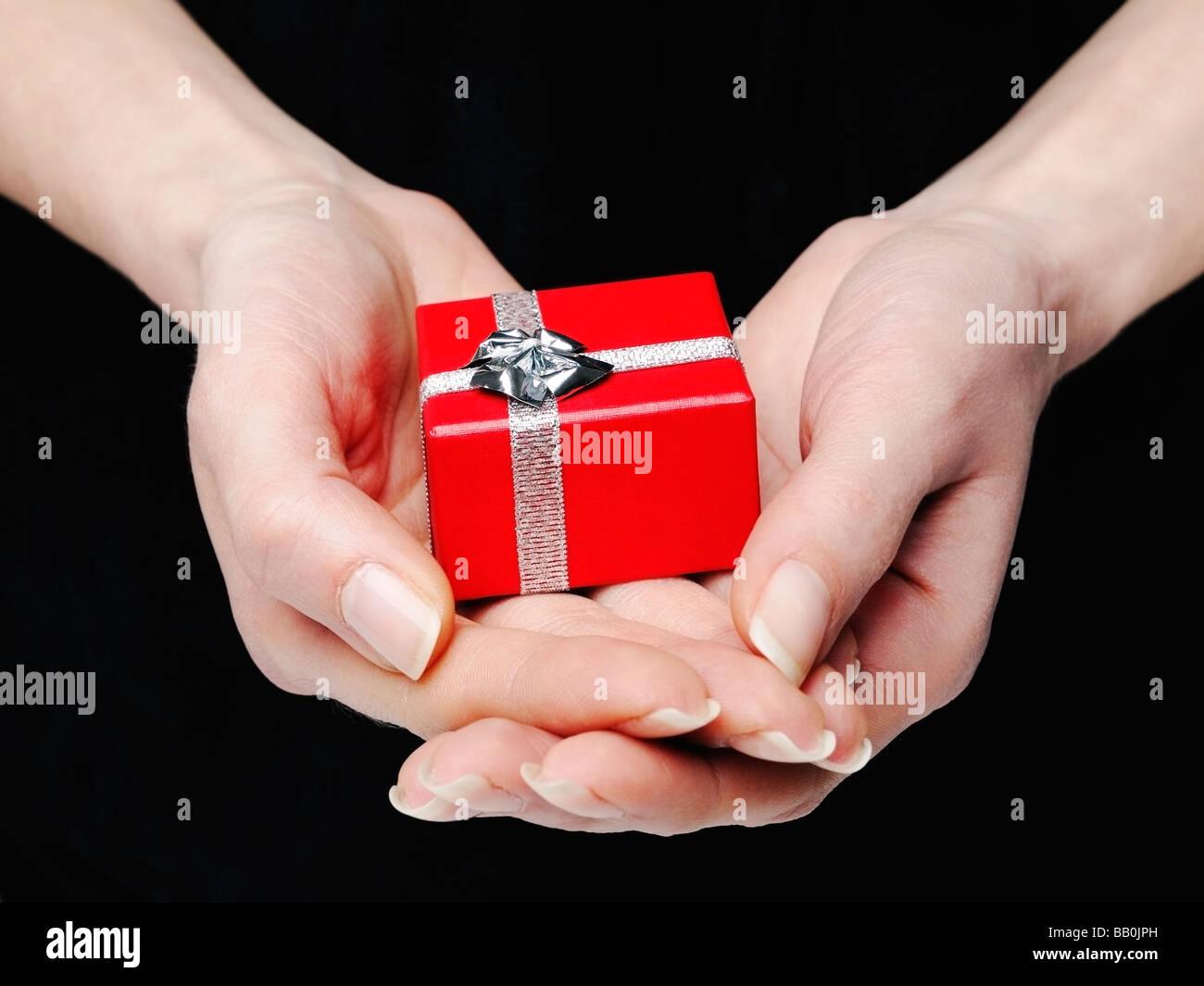 Mains tenant une boîte cadeau rouge Photo Stock