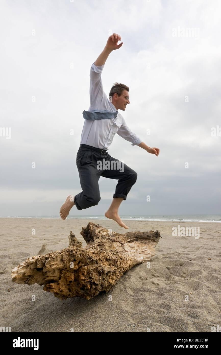 Businessman sautant par dessus un tronc d'arbre sur une plage Photo Stock