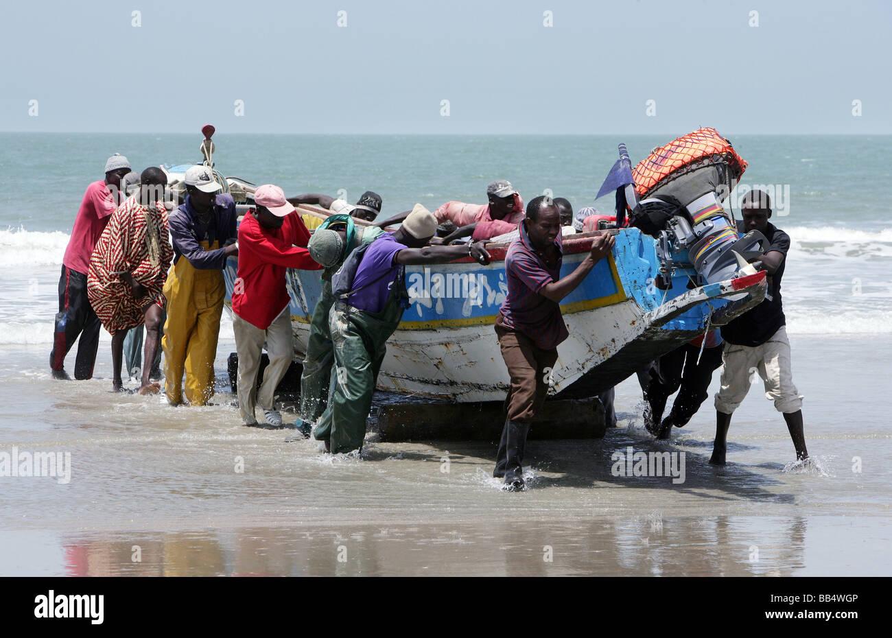 Les pêcheurs fournissent un bateau sur le rivage à Kap Skirring, au Sénégal Photo Stock