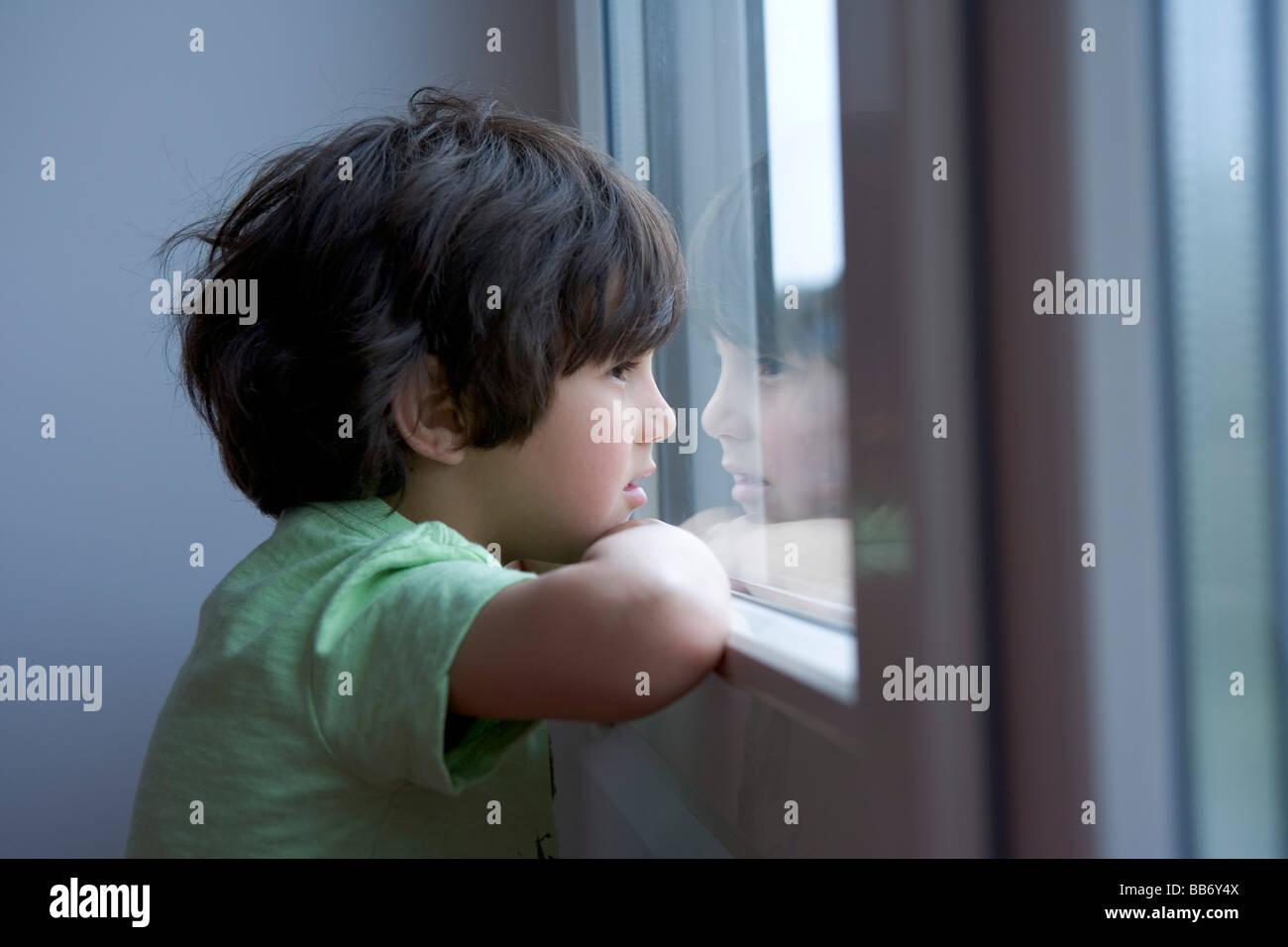 Petit garçon solitaire en regardant par la fenêtre Photo Stock