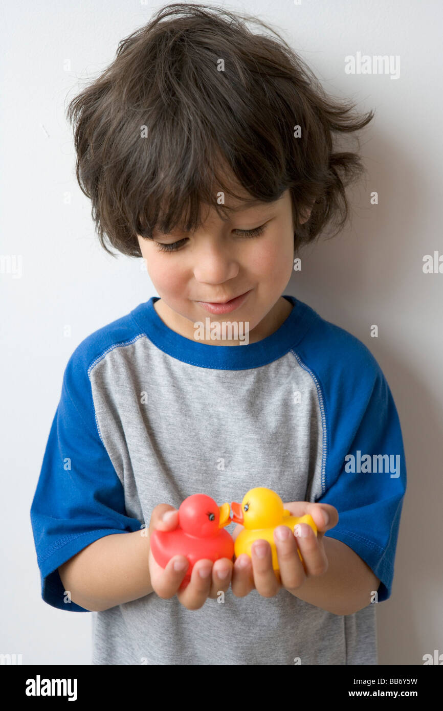 Petit garçon avec de petits canards en plastique Photo Stock