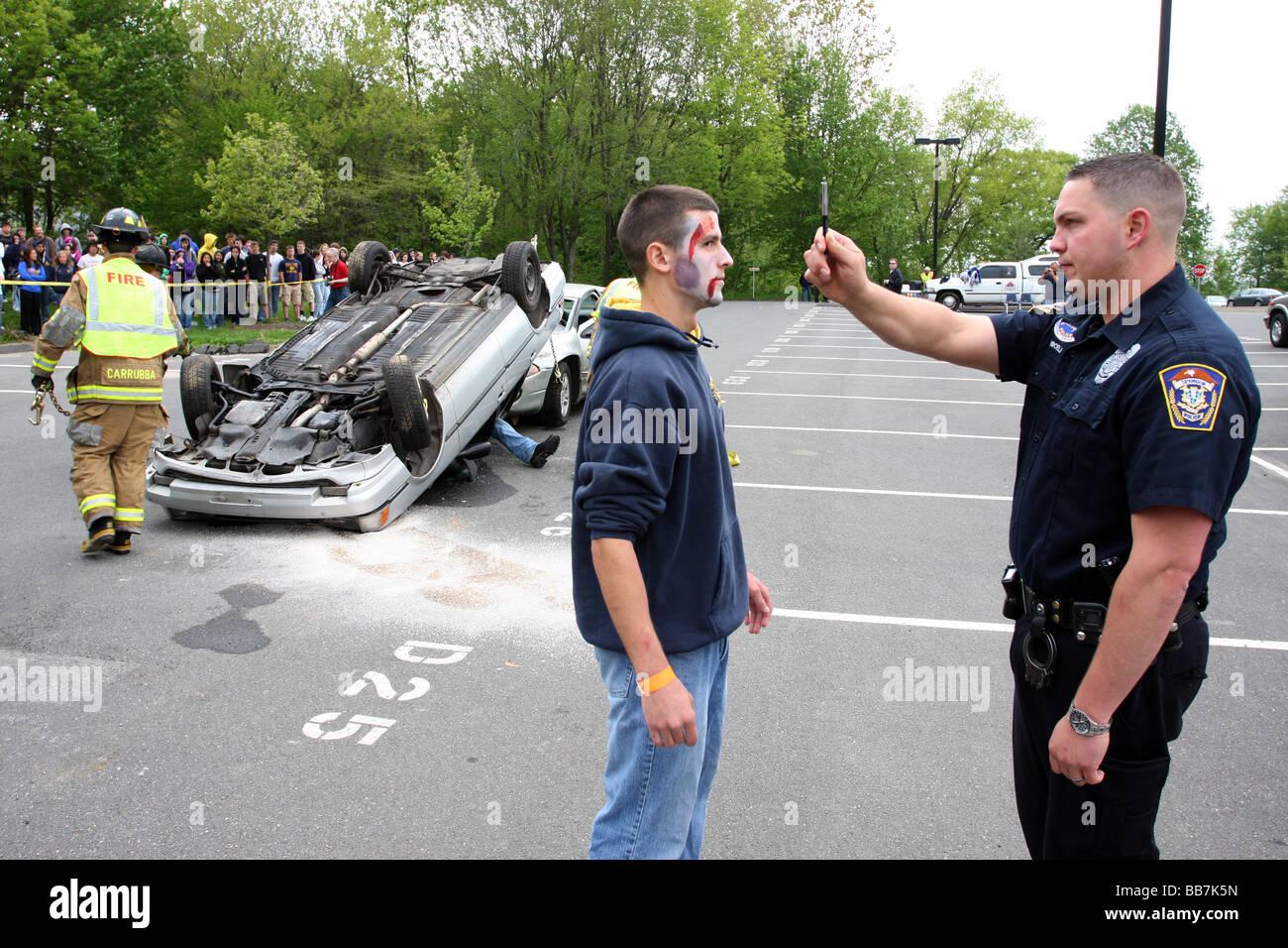 Un agent de police donne un adolescent un DUI test pendant une simulation d'alcool au volant accident à un USA High School Banque D'Images