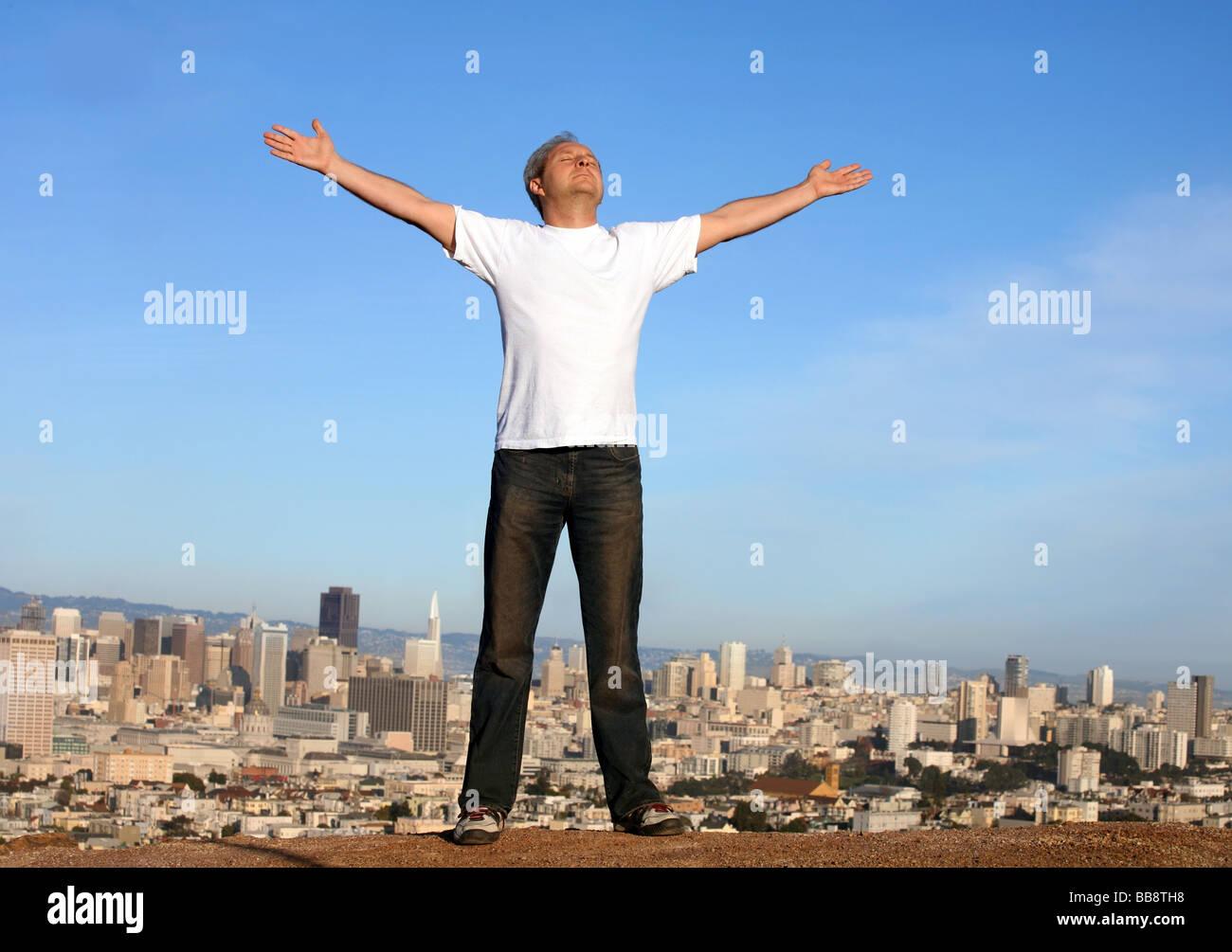 Un homme debout sur une colline avec une vue sur San Francisco son bras levés Photo Stock