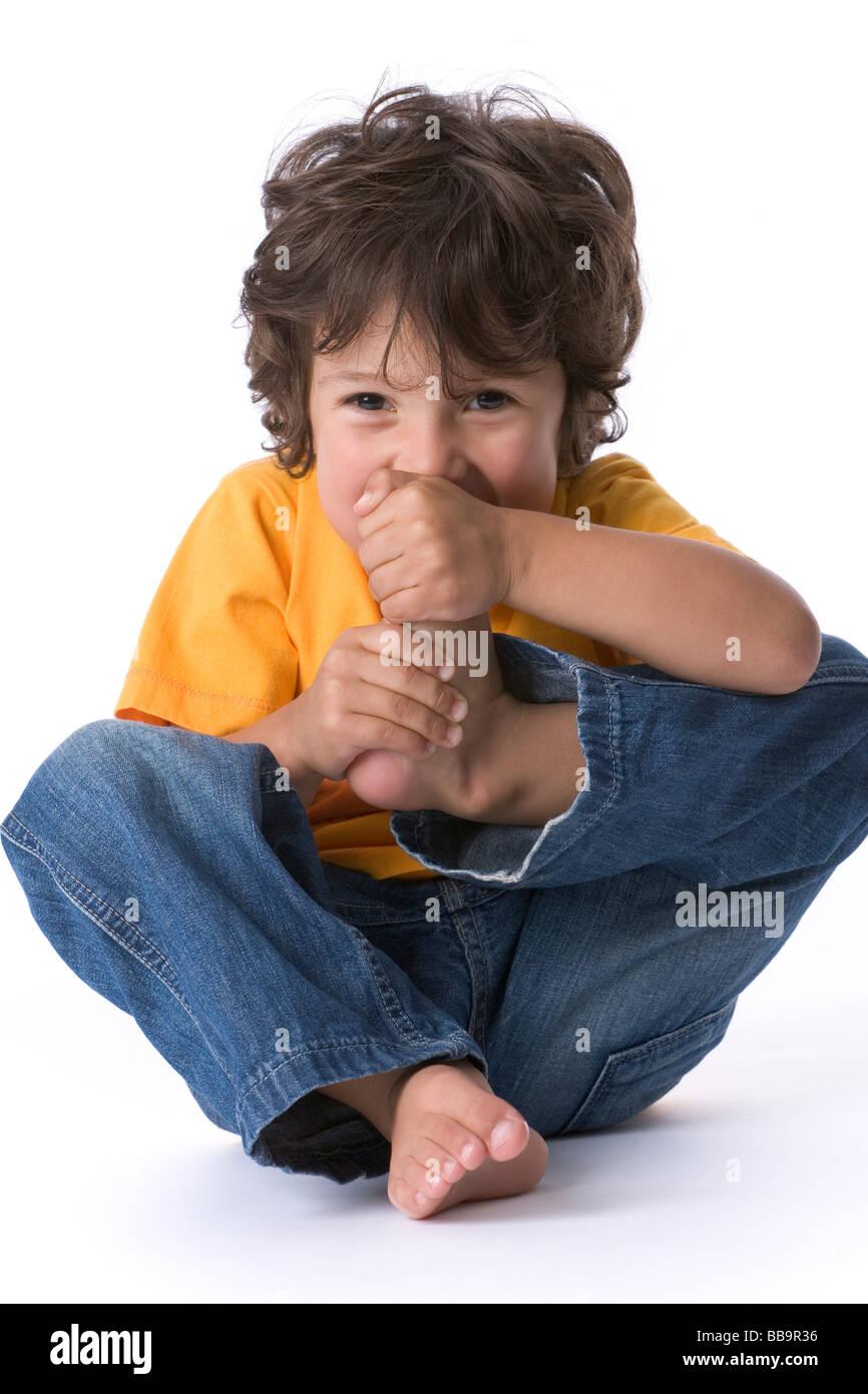 Petit garçon en train de manger son gros orteil comme plaisanterie Photo Stock