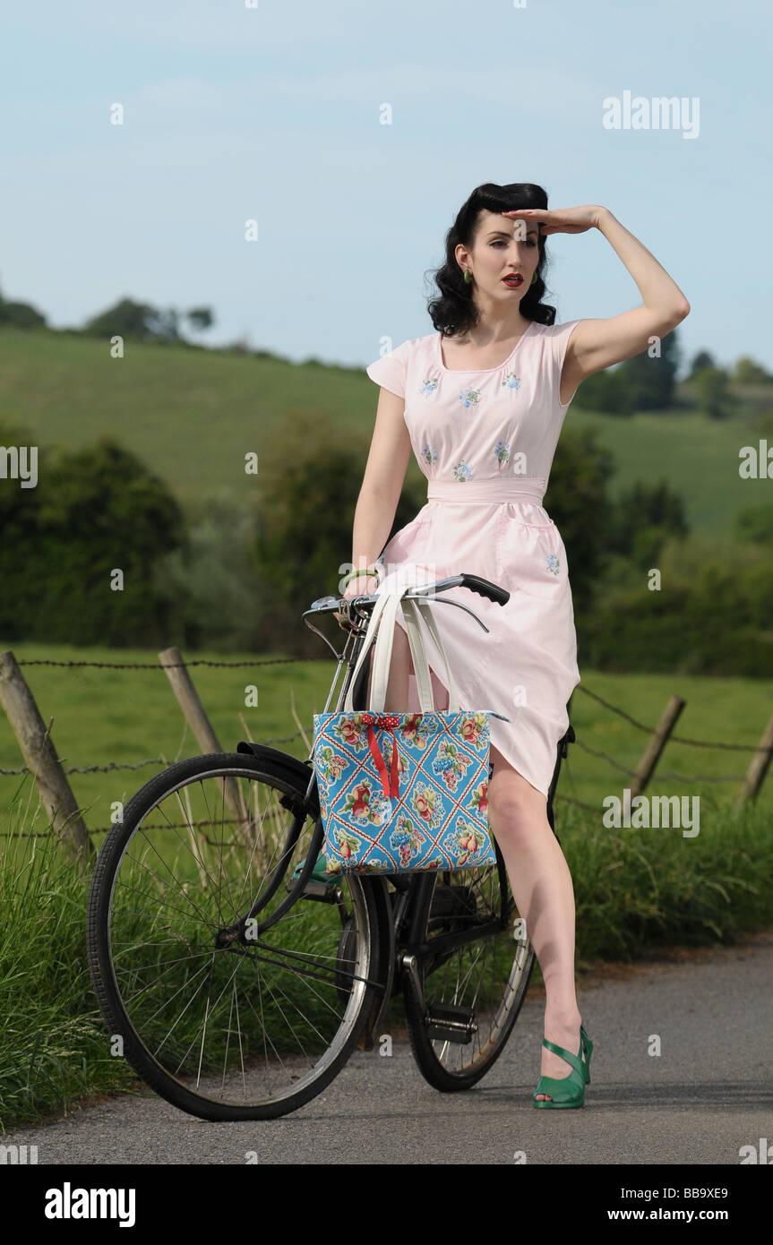 Femme portant des vêtements vintage sur un vieux vélo Photo Stock